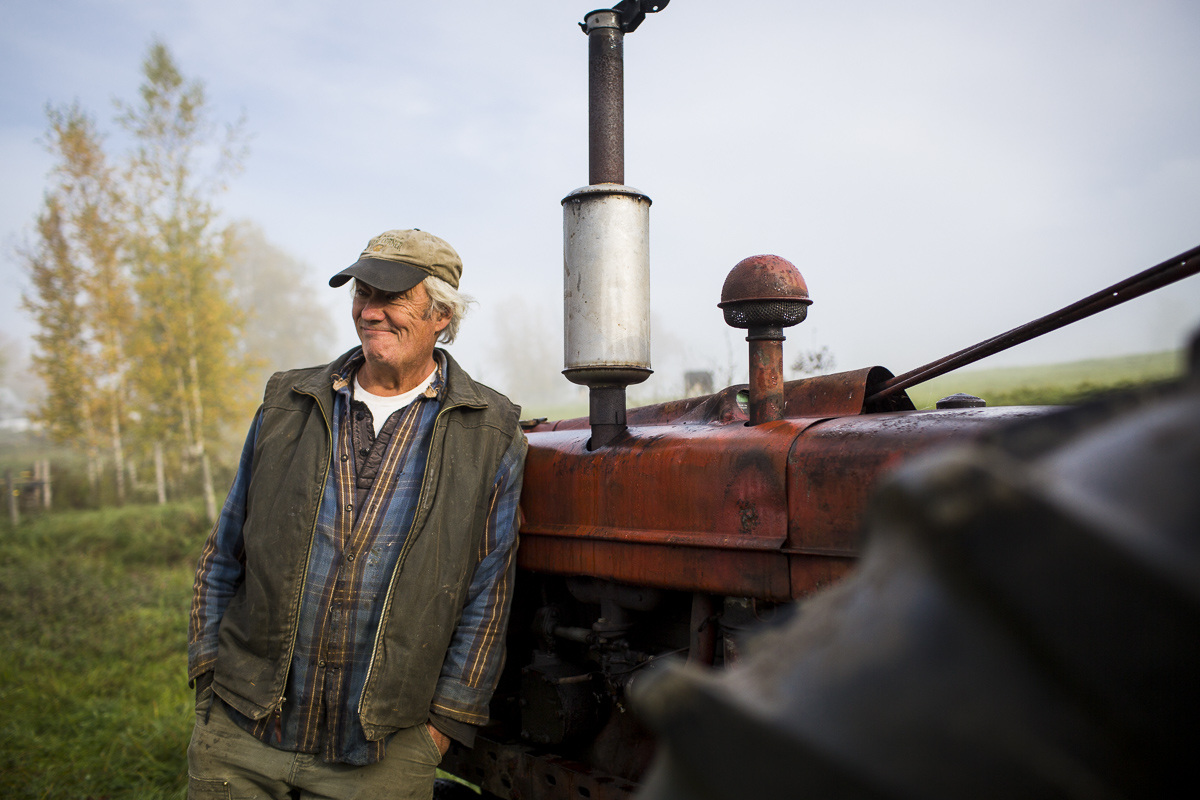 A fermer by his tractor during a guided tour with Country Walkers. by JAM Creative
