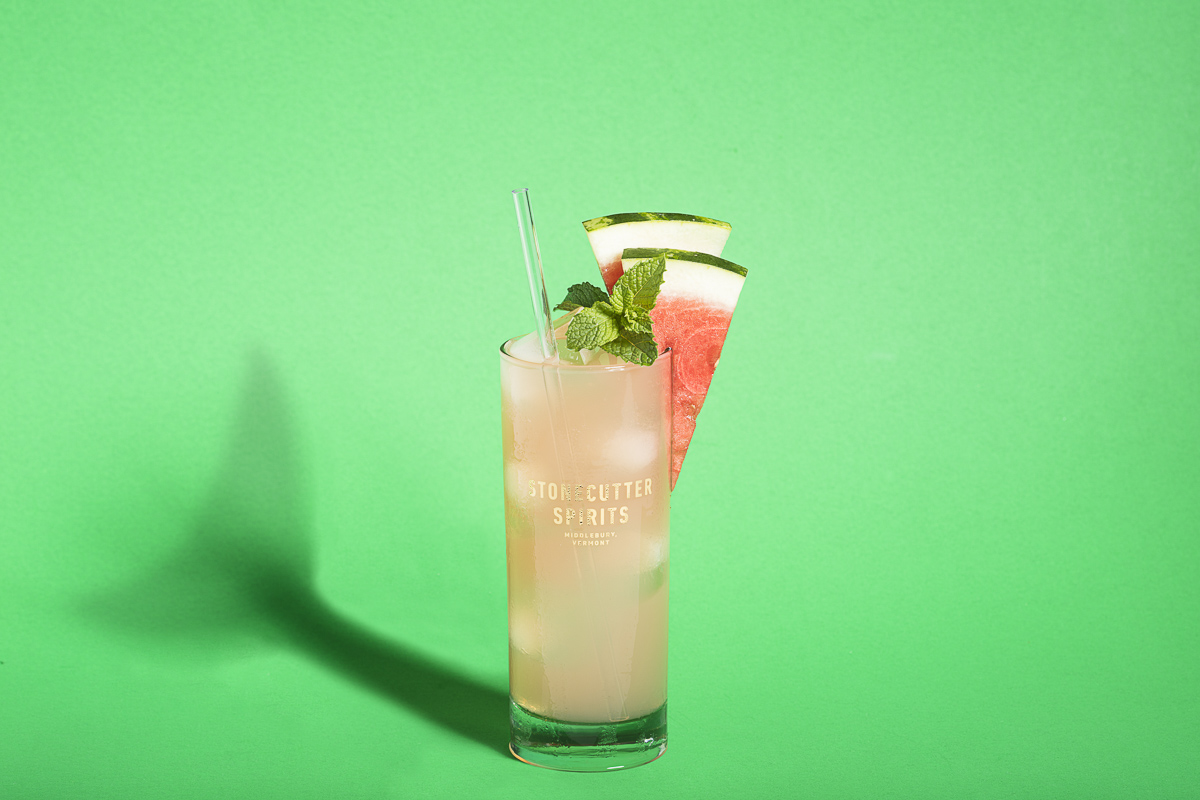 JAWS themed shark tail shadow and Stonecutter Spirits cocktail with watermelon on a green background. By commercial photographers at JAM Creative.