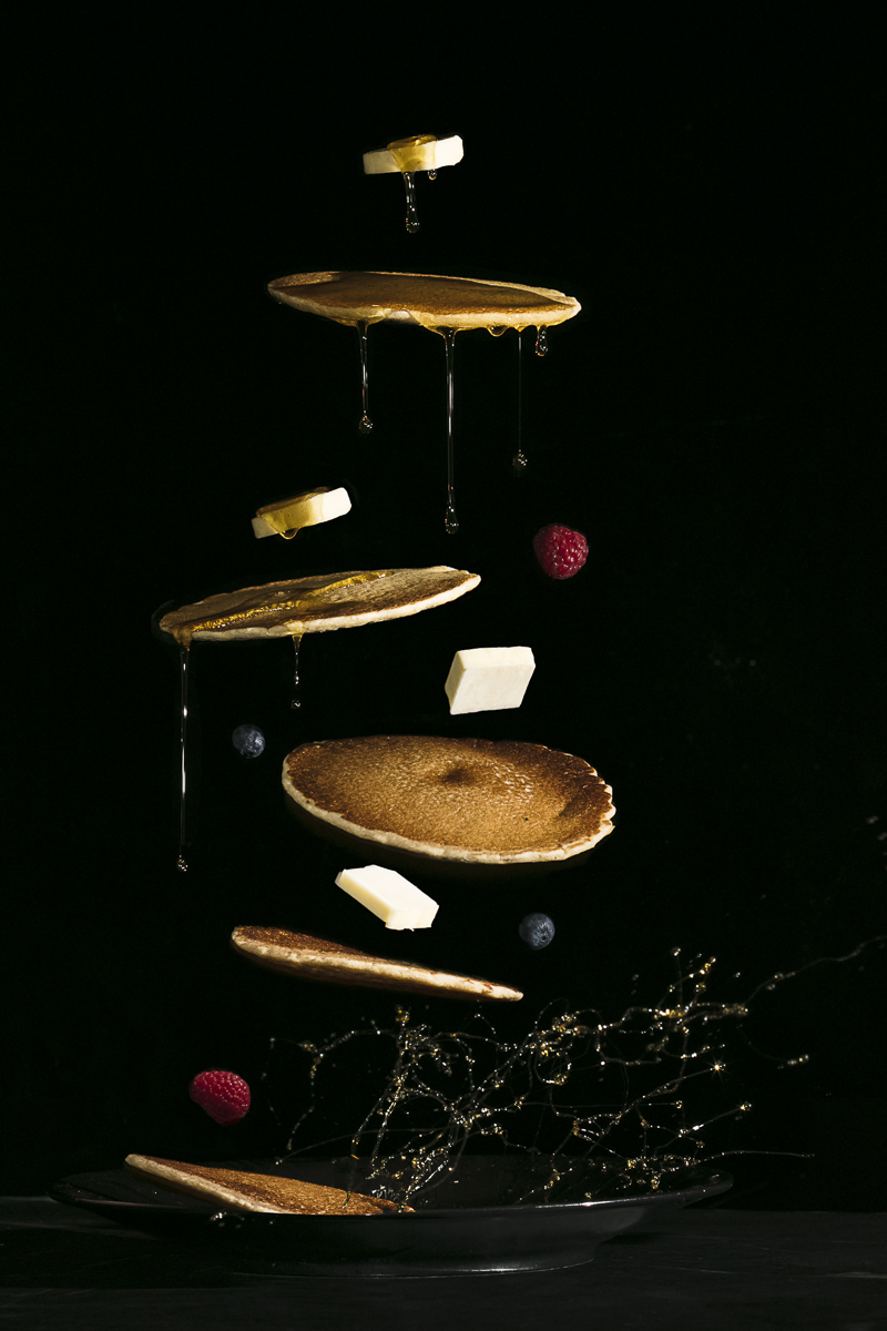 A deconstructed shot of a stack of pancakes with butter, maple syrup, and berries. For RunAmok Maple, by Jam Creative.