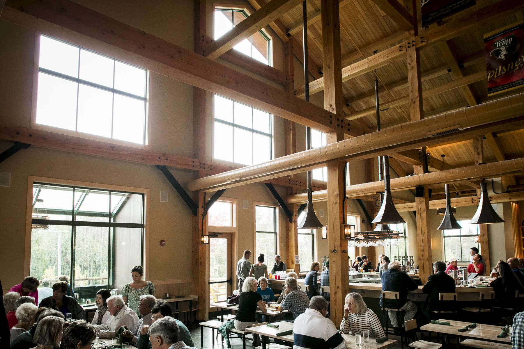 Gorgeous exposed beams tower above happy patrons enjoying local brews at Von Trapp Brewing Bierhall in Stowe, Vermont