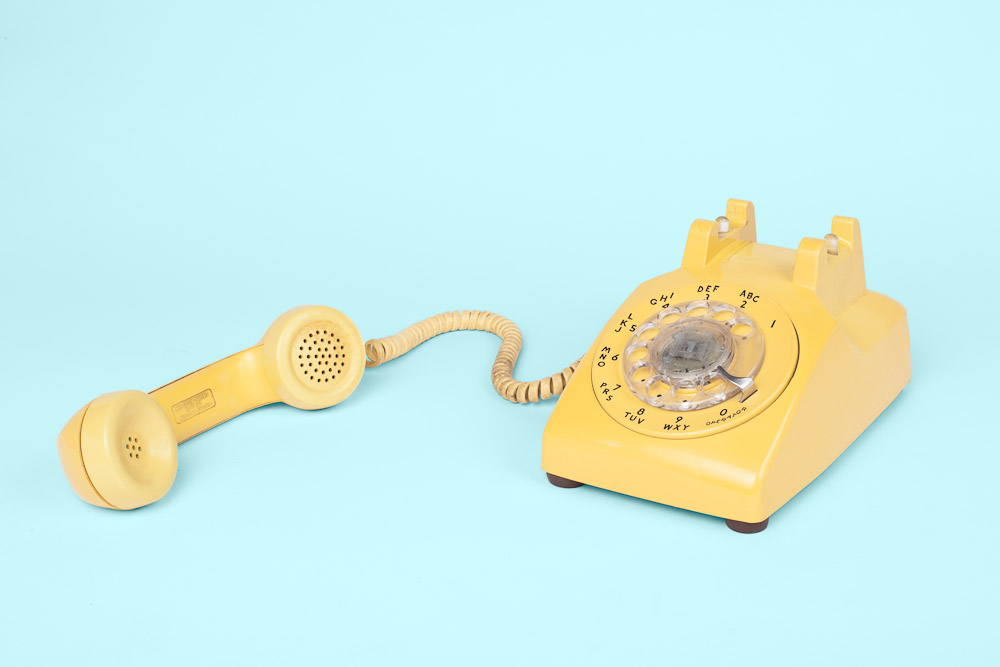 <p>Yellow rotary dial analog vintage phone off the hook shot in studio by Vermont photographers Reciprocity Studio in Burlington.</p>