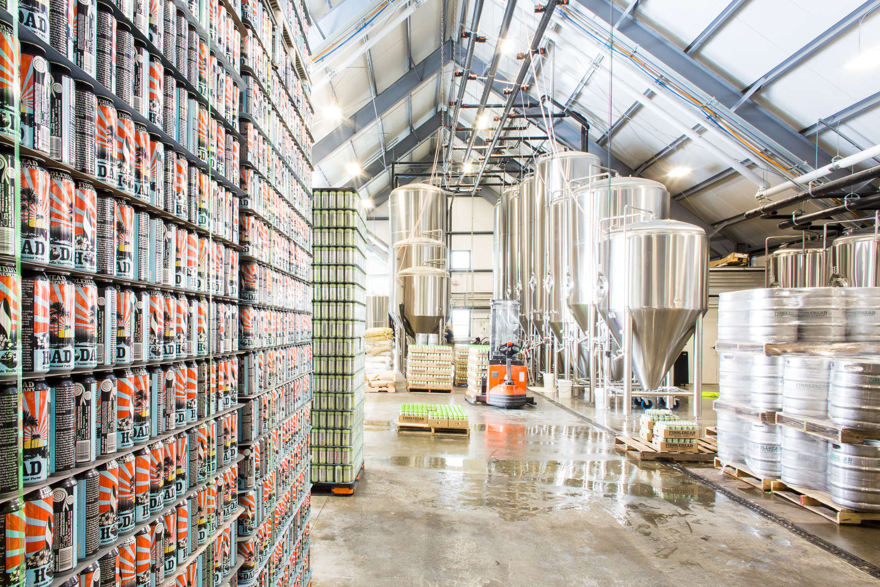 A bright and stunning photo of brewing tanks surrounded by cans of Fiddlehead Brewing Company's Hodad Porter.