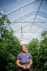 A greenhouse farmer poses with her homegrown vermont tomatoes.