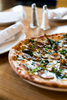 A tantalizing shot of a pizza sitting atop a perfectly set table by Jam Creative photography.