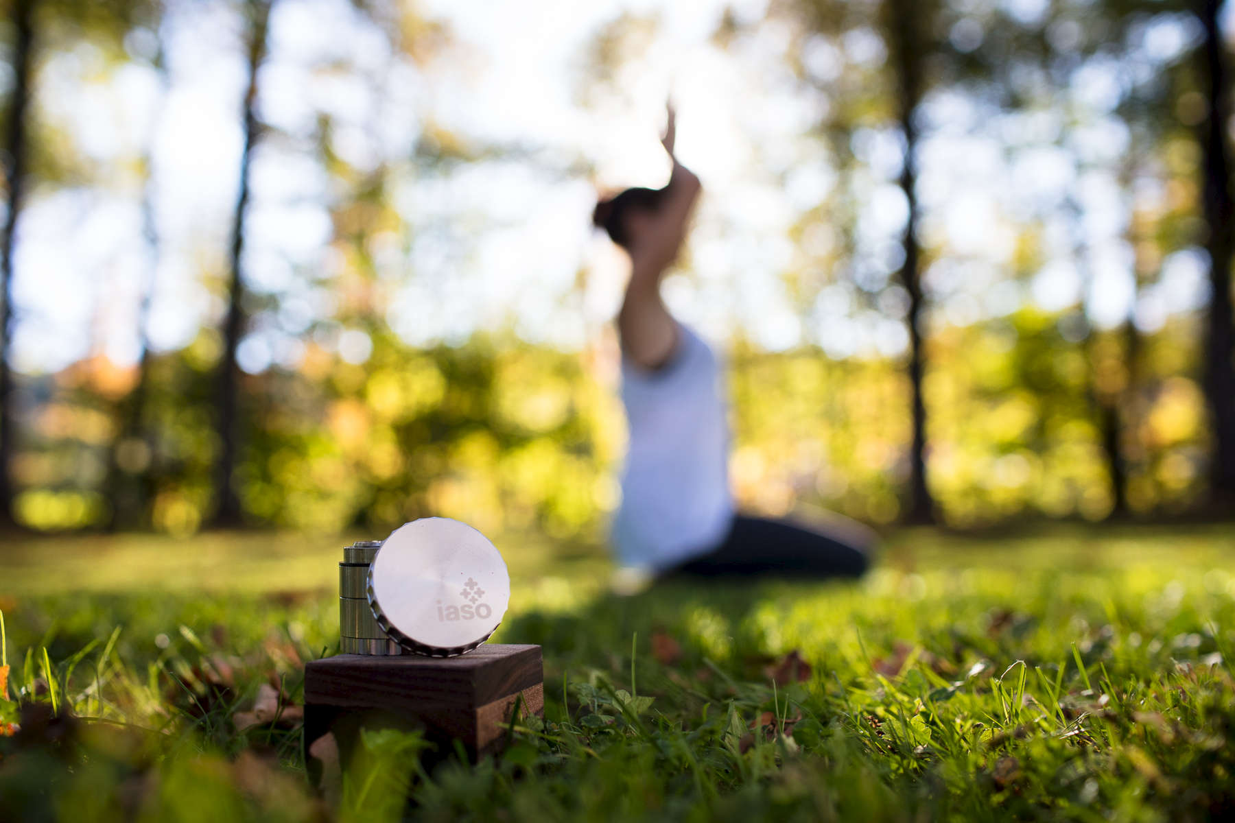 Unique product photo session with a IASO Goods cannabis grinder and a woman practicing yoga outside in Vermont.