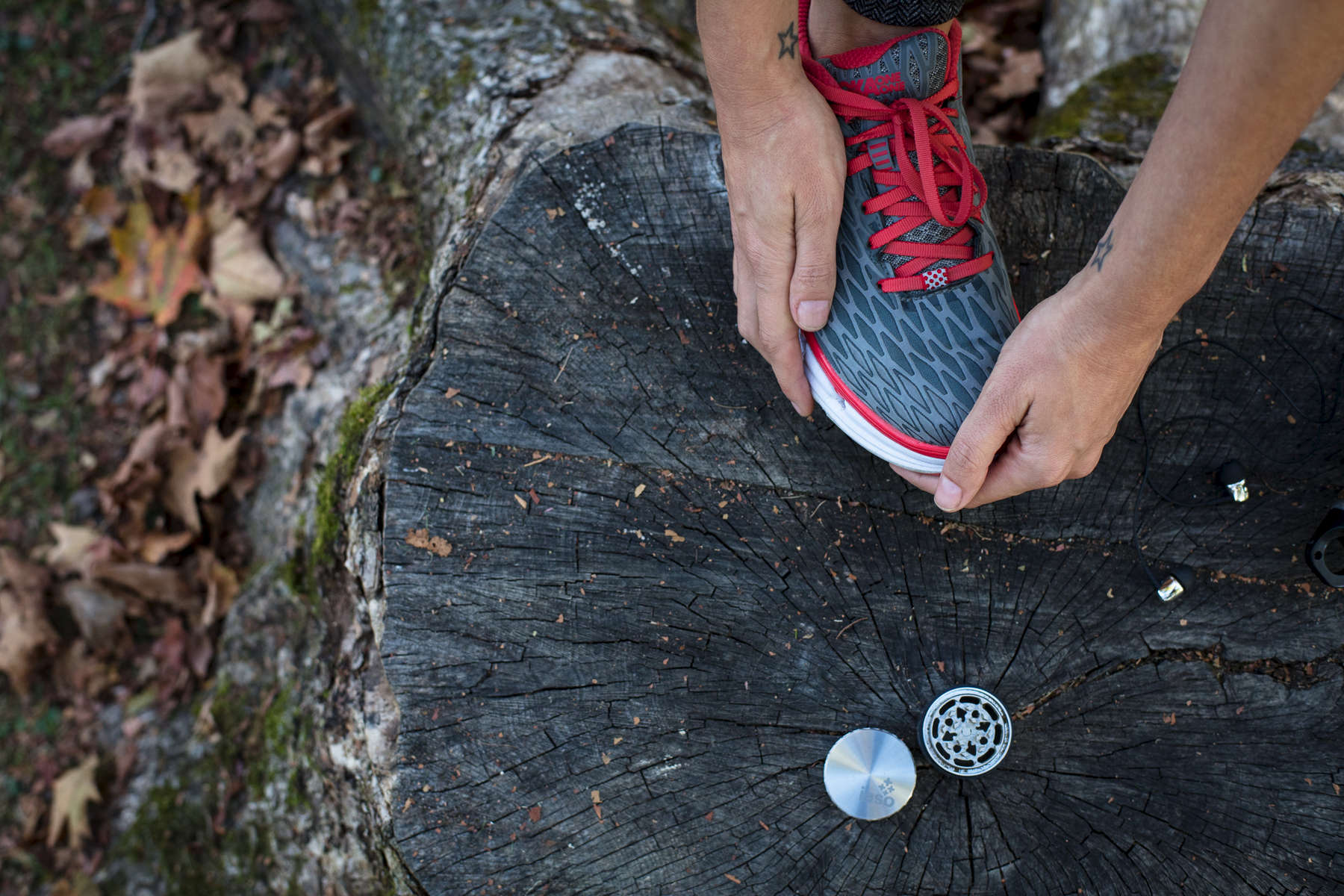 Woman athlete stretching during a jog, with IASO goods stainless steel cannabis grinder.