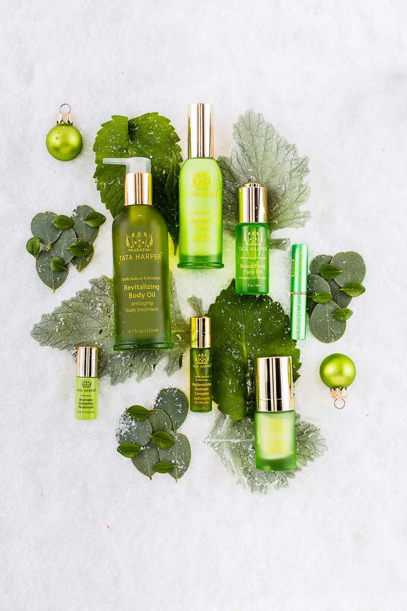 Tata Harper Revitalizing Body Oil, Aromatic Irritability Treatment, Beautifying Face Oil, Rejuvenating Serum and Replenishing Nutrient Complex with ornaments, green leaves and snow. Shot at Reciprocity Studio in Burlington, Vermont for Tata Harper Skin Care.