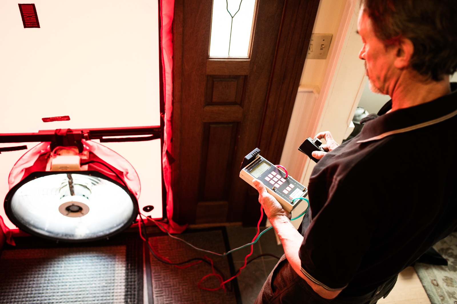 A contracter performs a home energy efficiency audit for a couple in Richmond, Vermont. by Reciprocity Studio photographers for Efficiency Vermont