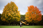 Young woman running with fabric between two trees in autumn, New England. by Vermont photographers at Reciprocity Studio, Burlington