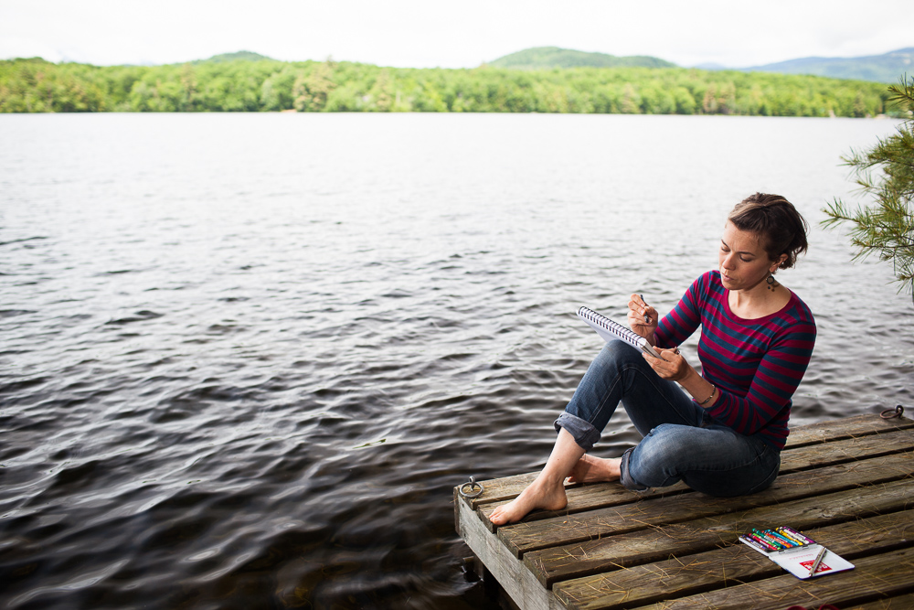 Young woman drawing on dock near lake water, by Vermont photographers at Reciprocity Studio, Burlington