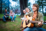 Young people playing guitar around a campfire. by Vermont photographers at Reciprocity Studio, Burlington