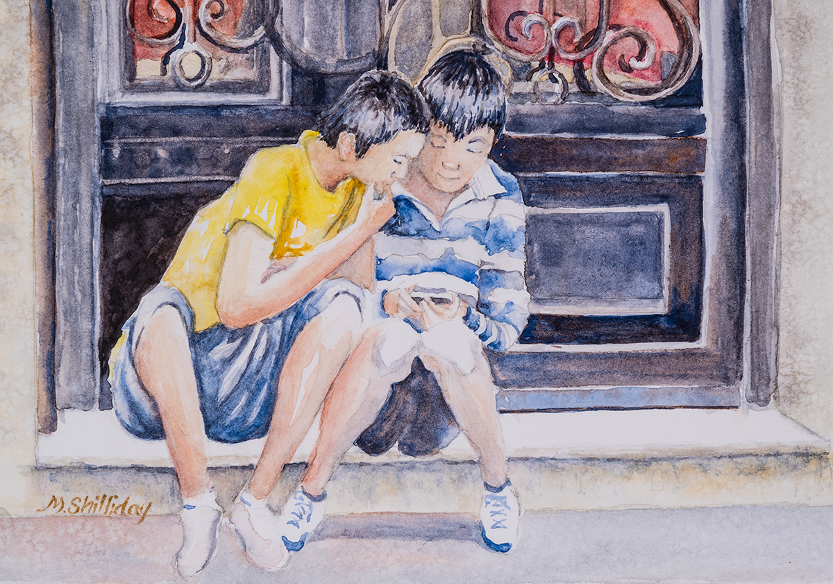 Asian boys playing with a cell phone, Madrid, Spain.