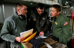 March Air Reserve Base C-17 aircrew Master Sgt. James, center, and Tech Sgt. Ryan Benson brief with Bill Taylor of McChord Air Force Base ground crew before loading humanitarian aid materials forHaiti after landing at McChord Air Force Base in Wash. (The Press-Enterprise/ Mark Zaleski)