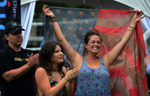 Kada Unwin, center, and Elizabeth Dowgin celebrate while listening to Danielle Peck perform at Transitions Performance Park during the 2013 CMA Music Festival in Nashville, Tenn. (The Tennessean/ Mark Zaleski)