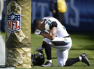 Jacksonville Jaguars running back Justin Forsett kneels by a Salute to Service logo on a goal post before an NFL football game between the Jaguars and the Tennessee Titans on Nov. 10, 2013, in Nashville, Tenn. (AP Photo/ Mark Zaleski)
