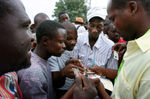 Haitian men gather around a man distributing identification cards needed to get work assisting in the humanitarian aid effort at Port-Au-Prince International Airport in Haiti. (The Press-Enterprise/ Mark Zaleski)