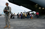 A United State Air Force security guard monitors the March Air Reserve Base C-17 aircraft while the crew boards evacuees at Port-Au-Prince International Airport in Haiti. (The Press-Enterprise/ Mark Zaleski)