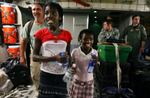 Doug Fry, left, and the two daughters he adopted, Jona Tyuste Fry, 12, and Ginette St-Louis Fry, 11, board the March Air Reserve Base C-17 before leaving Haiti. (The Press-Enterprise/ Mark Zaleski)
