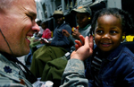 Scott Air Force Base Lt. Col. Randon Draper puts ear plugs in a Haitian girl in the cargo bay of a March Air Reserve Base C-17. (The Press-Enterprise/ Mark Zaleski)
