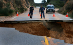 California Highway Patrol officers inspect a section of Highway 330 in the San Bernardino Calif., mountains after it was washed away during a rain storm. (The Press-Enterprise/ Mark Zaleski)
