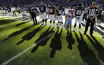 Tennessee Titans players take part in a moment of silence in tribute to the late Bum Phillips before an NFL football game against the San Francisco 49ers on Oct. 20, 2013, in Nashville, Tenn. Phillips, the former Houston Oilers head coach, died Oct. 18, 2013. (AP Photo/ Mark Zaleski)