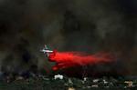 An air tanker drops fire retardant on flames behinda home in Oak Hills, Calif., during the Hill Fire. (The Press-Enterprise/ Mark Zaleski)