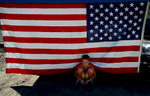 Jacob Burcham, 10, finds shade under an Americanflag that hangs from a Pop-Up shelter in the dirt and ash where his grandparents house was on Hook CreekRoad in Cedar Glen, Calif. The house was destroyed in the San Bernardino Old Fire last year. His grandparents, Janet and Jim Burcham, bought the house one week before the Old Fire burned through Cedar Glen. The Burchams were participating the Cedar Glen block partya year after the fire destroyed hundreds of homes. (The Press-Enterprise/Mark Zaleski)