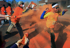 Tommy Barnes is sprayed from three directions by volunteers with powder at the orange color zone along Woodland Street during the 5K Color Run in Nashville, Tenn. (Mark Zaleski/ For The Tennessean)