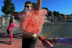 A participant covers his mouth while being sprayed with pink powder at the 3K mark along Russell Street during the 5K Color Run in Nashville, Tenn (Mark Zaleski/ For The Tennessean)