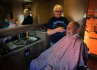Carl Hunt, a Barstow barber for 47 years, hopes he doesn't cut anything but hair from Wayne Soppelandas the train rocks back and forth on the tracks. Hunt offered to cut hair on the 1949 Overland Trail rail car barber shop during the Kelso Flyer train ride.(The Press-Enterprise/ Mark Zaleski)