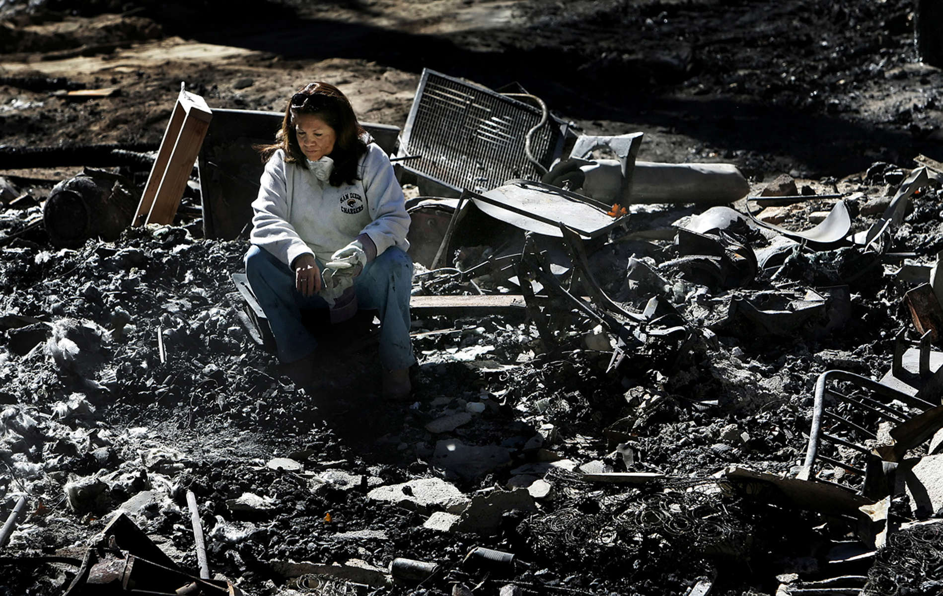 Tess Najarian sits in the rubble of her burned home on Holcomb Creek Drive while visiting the site for the first time since the Slide Fire destroyed it. Residents from Green Valley Lake, Calif., were allowed to see their neighborhood after mandatory evacuation restrictionswere lifted. (The Press-Enterprise/ Mark Zaleski)