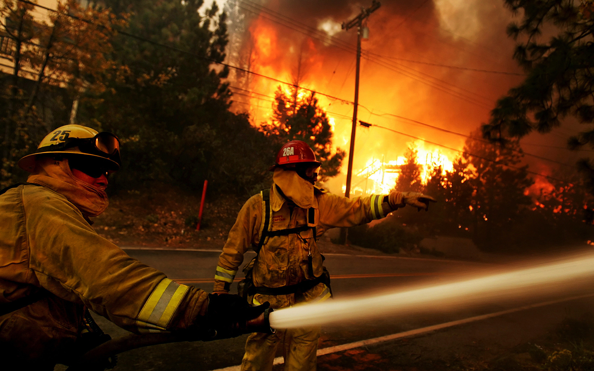 Firefighters spray water on a house trying to protect it while several other homes burn along Brentwood Lane in Lake Arrowhead, Calif., during the Old Fire. (The Press-Enterprise/ Mark Zaleski)