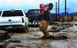 Redlands firefighter Chris Randolph rescues a woman from her car after a flash flood washed out San Timoteo Canyon Road in Redlands, Calif. Six cars were stuck in mud and debris from the flash flood. (The Press-Enterprise/ Mark Zaleski)