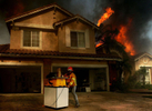 An off-duty firefigther takes out personal belongings from a house along Big Horn Mountain Way duringthe Freeway Complex Fire in Yorba Linda Calif. (The Press-Enterprise/ Mark Zaleski)