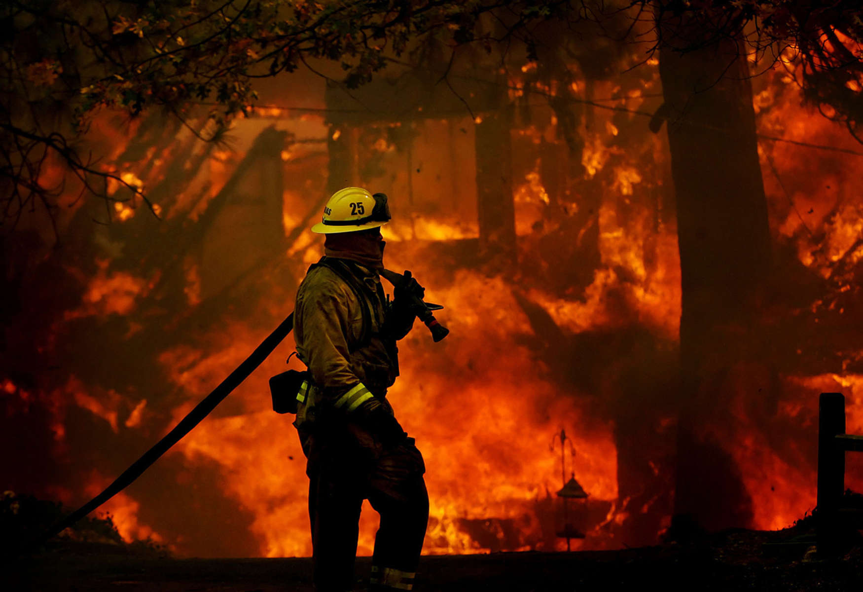 A firefighter moves his hose line away from a burning house along Brentwood Lane while battling the Grass Valley Fire in Lake Arrowhead, Calif. (The Press-Enterprise/ Mark Zaleski)