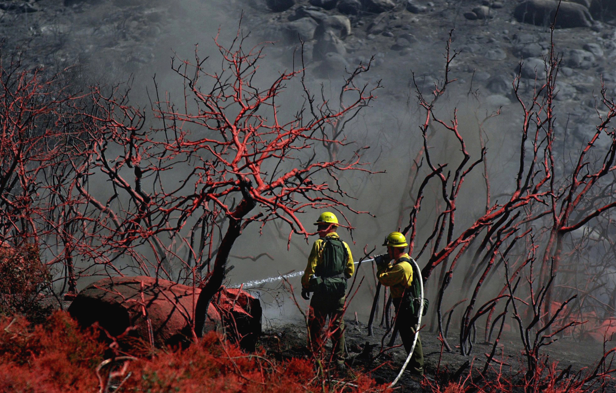 Firefighters extinguish a small spot fire after fire retardant was dropped along Highway 243 near Poppet Flat Road near Twin Pines, Calif. More than 200 acres were burned. (The Press-Enterprise/ Mark Zaleski)