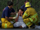 A woman is comforted by Riverside County and Colton City firefighters after learning her daughter died in a single car rollover on Interstate 215 in Colton, Calif.(The San Bernardino Sun/ Mark Zaleski)