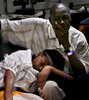 A man comforts his sick wife while in the cargo bay after being evacuated from Port-Au-Prince Haiti.190 evacuees will be flown to Orlando Sanford International  Airport in Fla. to stay with relatives or family members.  (The Press-Enterprise/ Mark Zaleski)