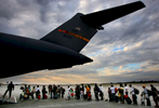Evacuees heading to the United States line up on the tarmac to board the C-17 in Haiti. Base crew then helped evacuate orphans meeting their new familiesin the U.S. (The Press-Enterprise/ Mark Zaleski)