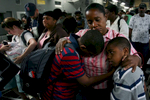 Daphnee Toban hugs her children Olivier Carl, left, and Sebastian Charles in the cargo bay of a March Air Reserve Base C-17 aircraft after arriving at Orlando Sanford International Airport in Fla. Daphnee's children were visiting their grandmother in Haiti when the earthquake hit. (The Press-Enterprise/ Mark Zaleski)