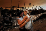 Bruce Milne, left, comforts his wife, Melanie, after his metal shop was destroyed by the Sawtooth Fire. Their home on Lariat Trail was spared by the fire storm that hit Pioneertown in Yucca Valley, Calif. The firedestroyed more than 50 homes and buildings. (The Press-Enterprise/ Mark Zaleski)