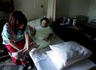 Certified nursing assistant Gloria Woods, helps Lois Scott, 78, into bed after having lunch in her room on the skilled nursing floor. (The Press-Enterprise/ Mark Zaleski)