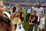 Washington Redskins quarterback Robert Griffin III poses for photos with fans before a preseason NFL football game against the Tennessee Titans on Aug. 8, 2013, in Nashville, Tenn. (AP Photo/ Mark Zaleski)