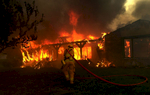 San Manuel firefighter Laurie Green movesin to extinguish a house engulfed in flamesin San Bernardino, Calif. Hundreds of homes were destroyed in the Old Fire. (The Press-Enterprise/ Mark Zaleski)