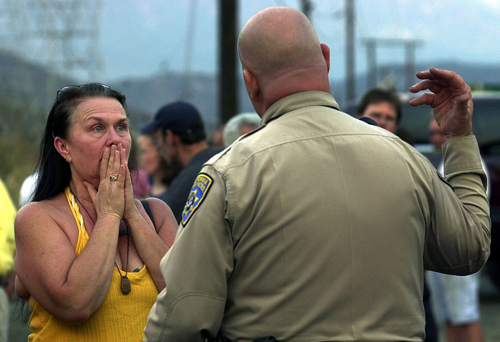 California Highway Patrol Officer C.A. Dosstells Terria Robertson that she can't go back to her home on Sycamore Drive because the Grand Prix Fire is burning in Lytle Creek, Calif. (The Press-Enterprise/ Mark Zaleski)