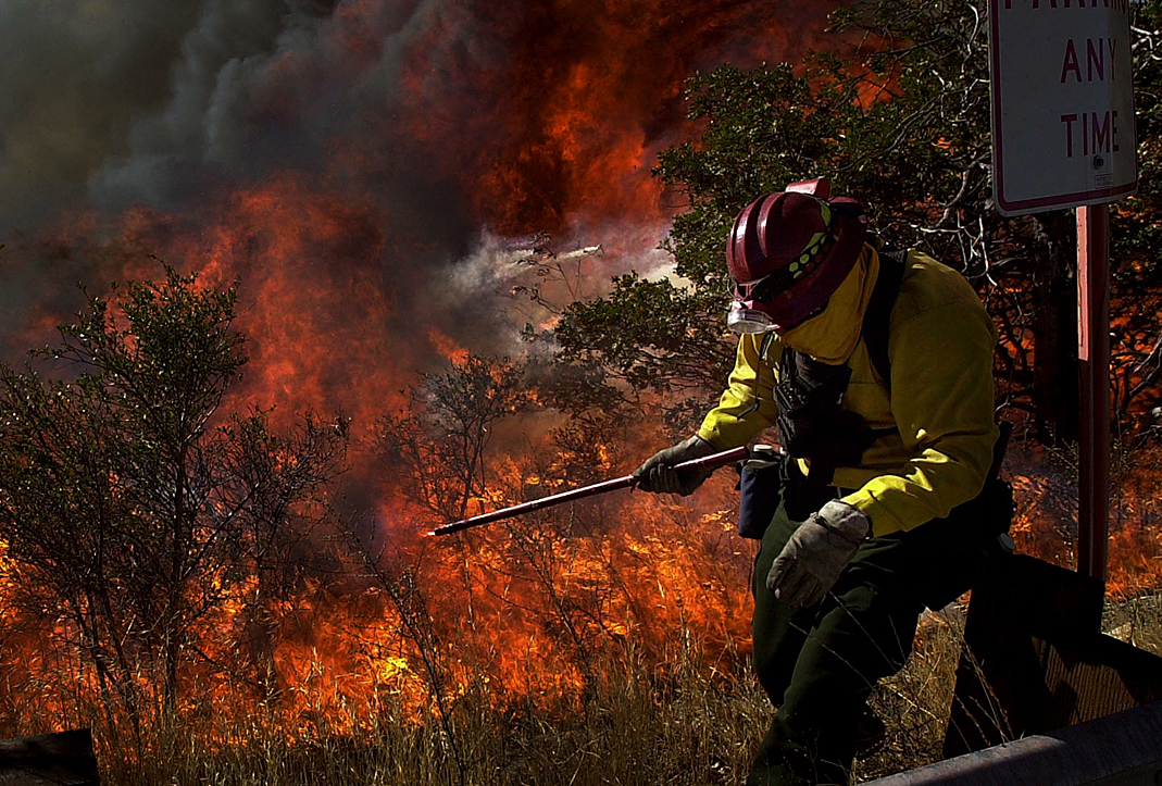 San Bernardino, Calif., city firefighter Paul Drasil moves quickly out of the way from flames after lighting back fires along Highway 18 during the Old Fire. (The Press-Enterprise/ Mark Zaleski)