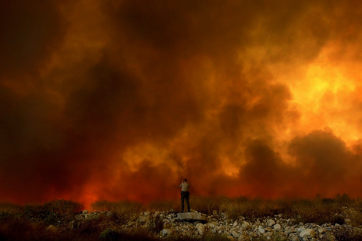 San Bernardino County Sheriff Deputy Steve Cline watches the progress of the Grand Prix fire in Rancho Cucamonga, Calif. (The Press-Enterprise/ Mark Zaleski)