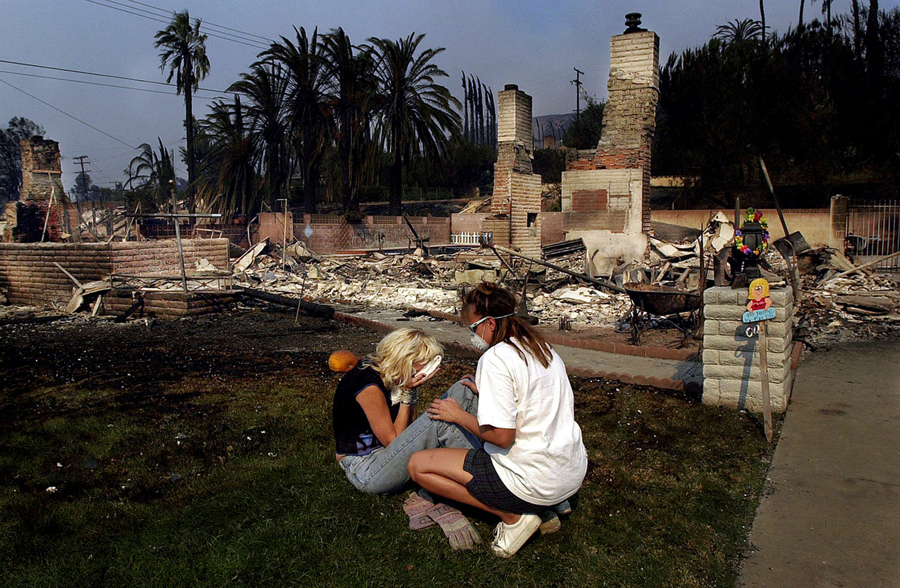 Tami Goldstein, left, starts to cry after going throughwhat is left of her home on Ralston Avenue after the Old Fire moved through the Del Rosa area of SanBernardino, Calif. (The Press-Enterprise/ Mark Zaleski)