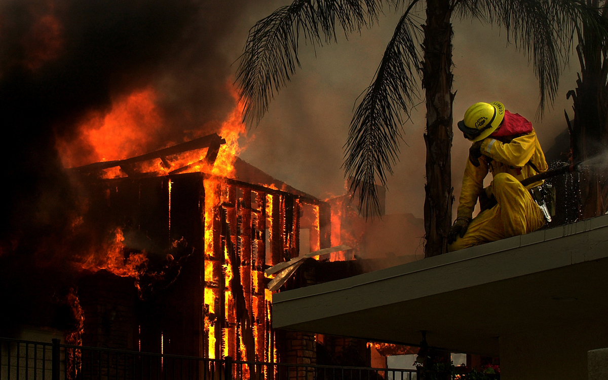 A firefighter pauses as a house next to theone he is protecting burns on Park Avenue during the Old Fire in San Bernardino, Calif. (The Press-Enterprise/ Mark Zaleski)