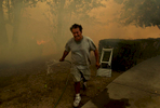 Joe Botello runs away from smoke and flames approaching his house on 54th Street in SanBernardino, Calif. Botello returned days later to find that his house was destroyed in the Old Fire. (The Press-Enterprise/ Mark Zaleski)